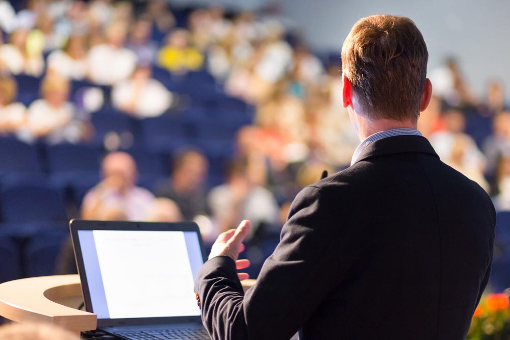 man at podium giving important sales presentation at event